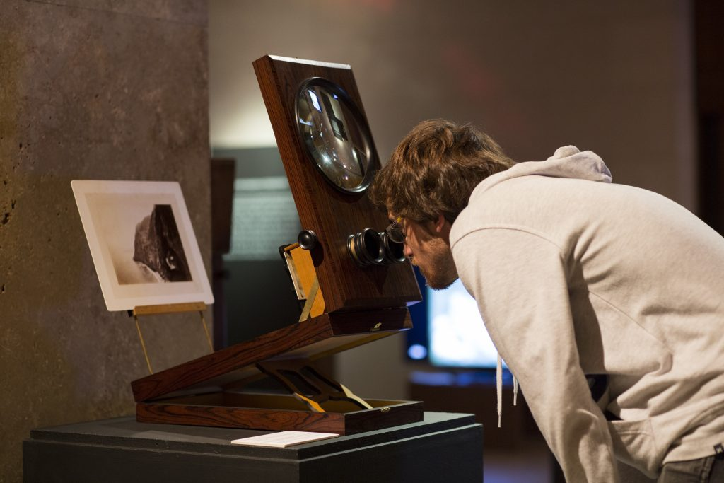 A visitor peeping in a stereo graphoscope